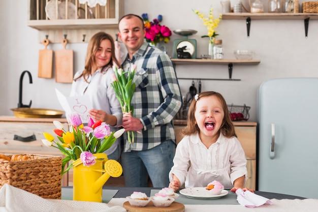 Hija graciosa haciendo cupcake cerca de padres con tarjeta de felicitación