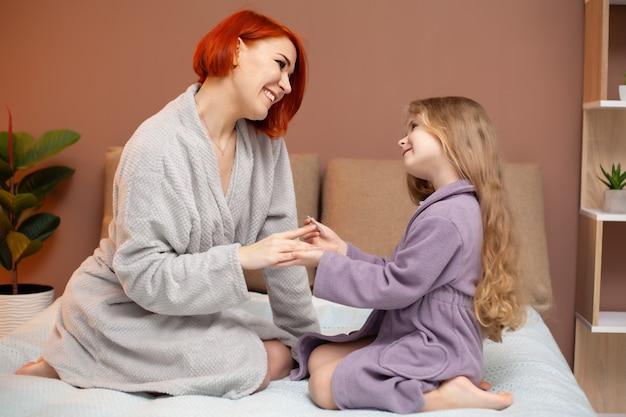 Hija hace manicura a mamá en casa en la cama