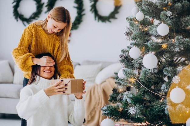 Hija haciendo presente sorpresa para madre en navidad
