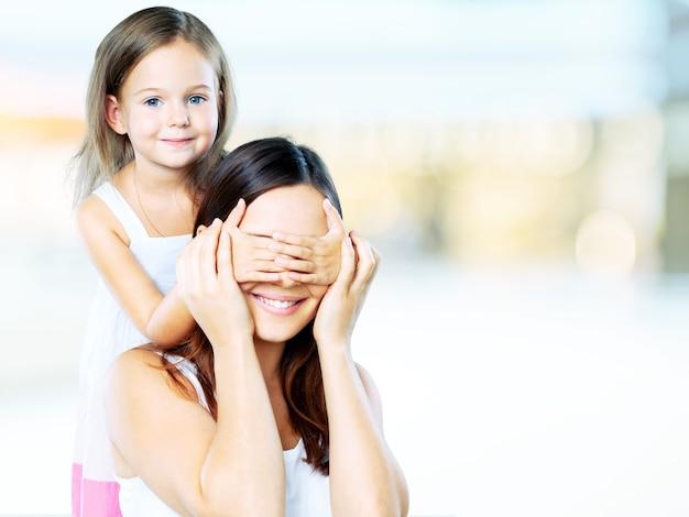 La hija joven cierra los ojos de la mamá de las manos - aislada. concepto de familia feliz.