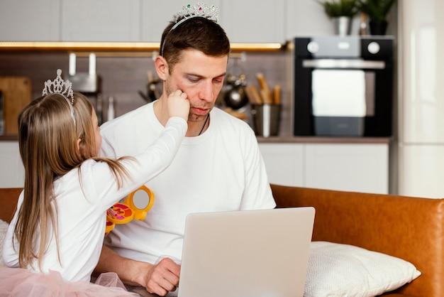Hija jugando con el padre mientras trabaja en la computadora portátil