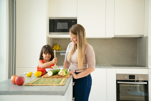 Hija linda ayudando a mamá a cocinar la cena. niña y su madre tirando ensalada en la cocina con verduras cortadas. copie el espacio. concepto de cocina familiar