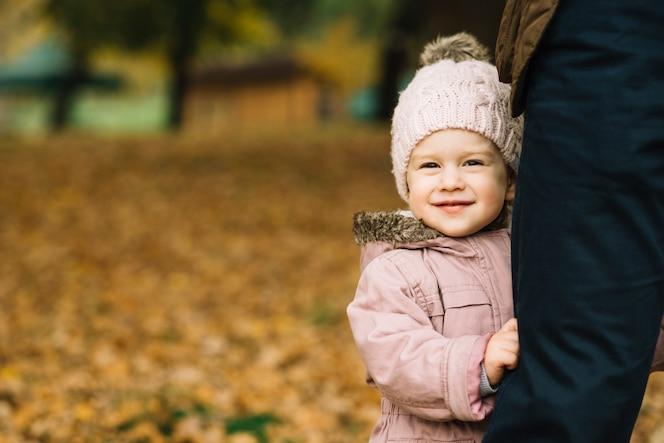 Hija linda que se sostiene en la pierna del padre en parque del otoño
