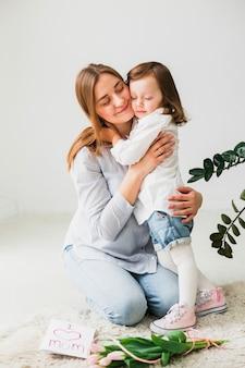 Hija y madre abrazando cerca de tarjeta de felicitación