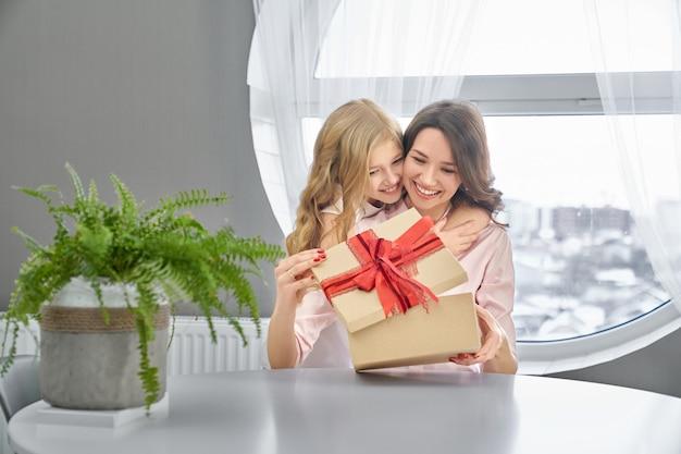 Hija y madre abrazándose y sonriendo.