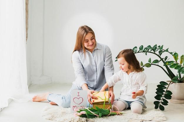 Hija y madre abriendo caja de regalo