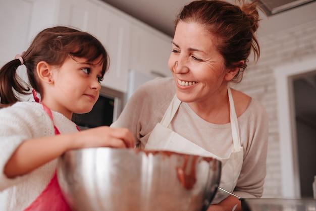 Hija y madre cocinando en casa un delicioso postre para el día de la madre