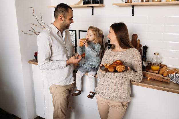 Hija con madre comiendo croissants. familia feliz en la cocina