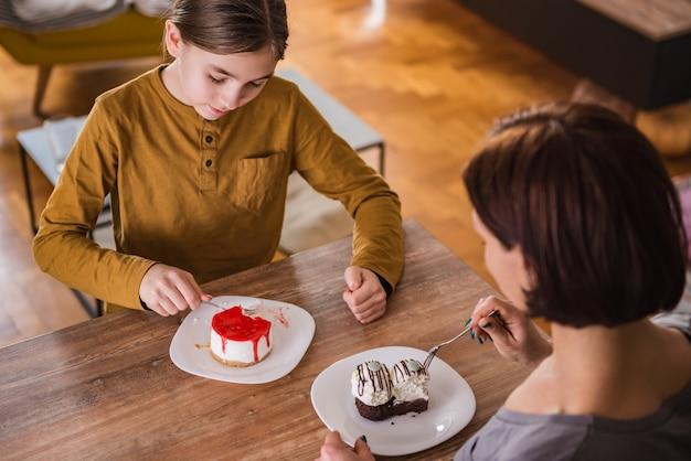 Hija y madre comiendo pastel en casa