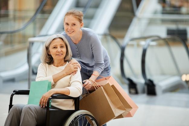 Hija con madre discapacitada yendo de compras