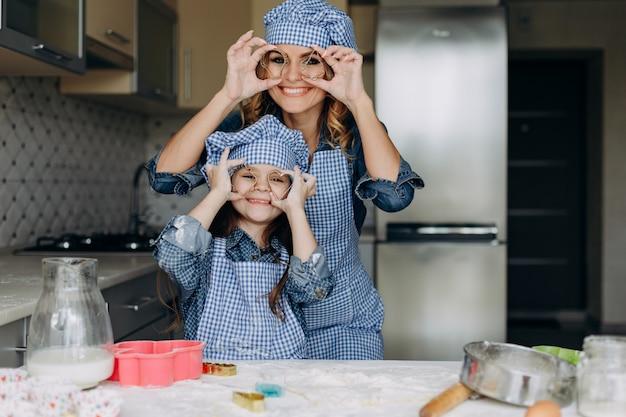 Hija y madre se divierten en la cocina. - imagen
