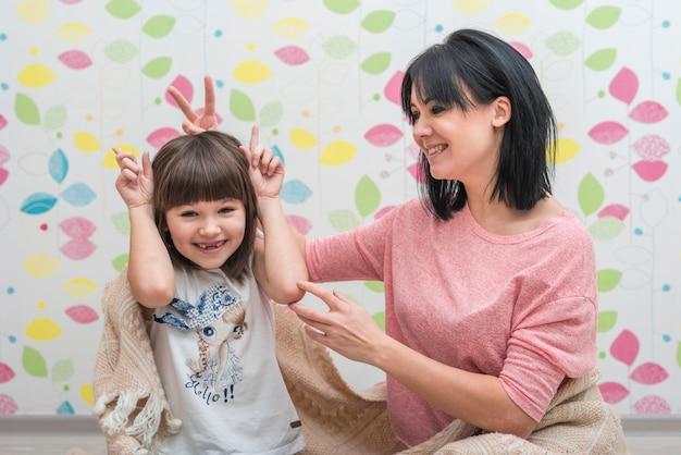 Hija y madre haciendo cuernos con los dedos.