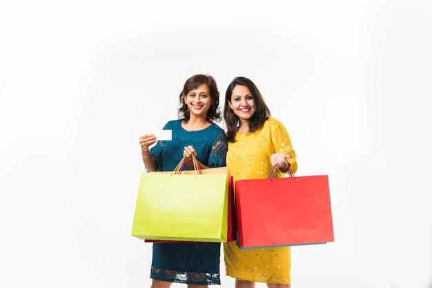 Hija de madre india hermanas compras con bolsas de colores, que se encuentran aisladas sobre fondo blanco.