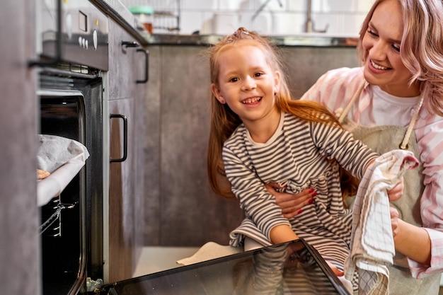 Hija y madre sacando la bandeja de galletas horneadas del horno en la cocina, la familia en casa, hornear y cocinar concepto