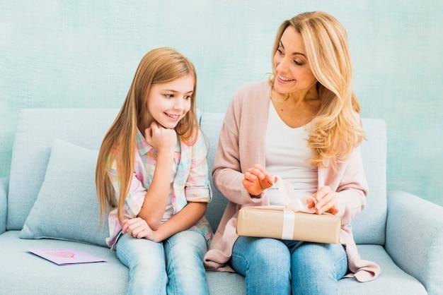 Hija y madre sentadas juntas y abriendo regalo.