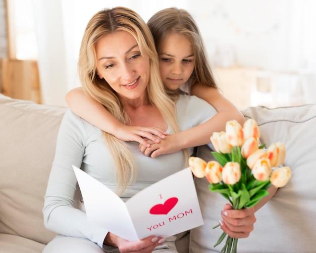 Hija madre sorprendente con ramo de tulipanes y tarjeta