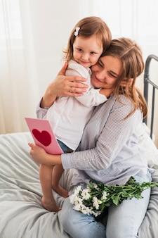 Hija y madre con tarjeta de felicitación abrazando