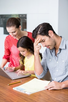 Hija y madre trabajando en la computadora portátil con tenso padre sentado en el escritorio
