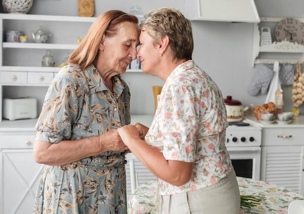 Hija madura que consuela a su madre mayor que lleva a cabo la mano en casa