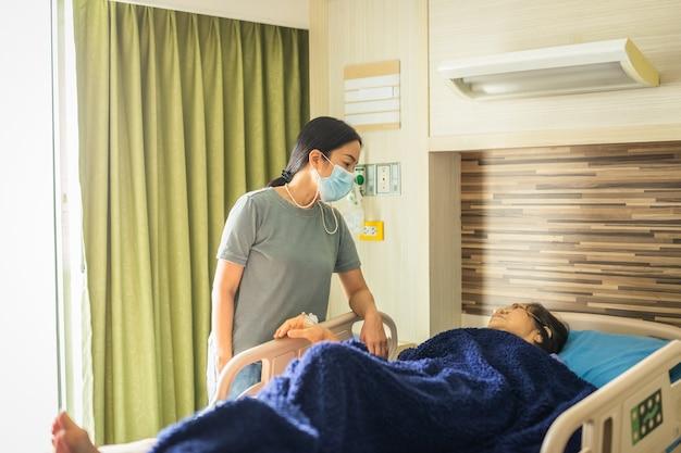 Hija en máscara médica visitando a su madre acostada en la cama en la sala del hospital