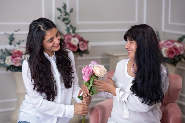 Hija mexicana entregando flores a su madre el día de la madre