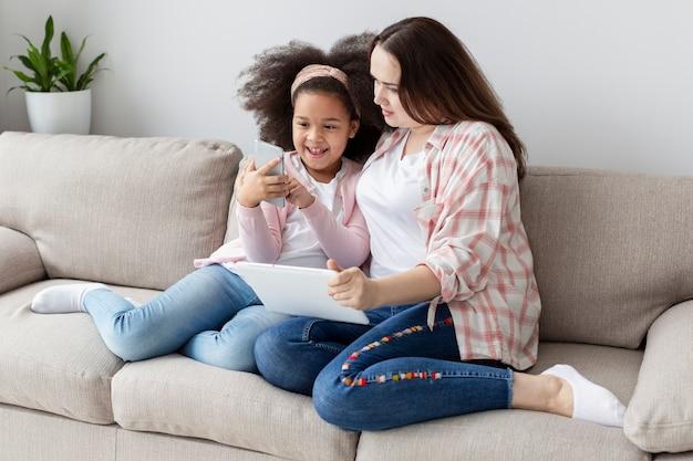 Hija mostrando algo en el teléfono a la madre