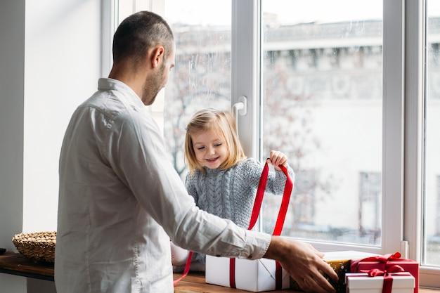 Hija y padre desempacando regalos cerca de la ventana