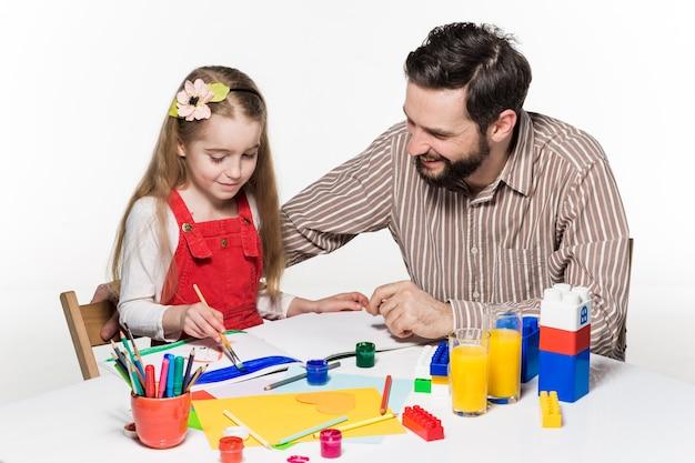 La hija y el padre dibujando y escribiendo juntos sobre fondo blanco.