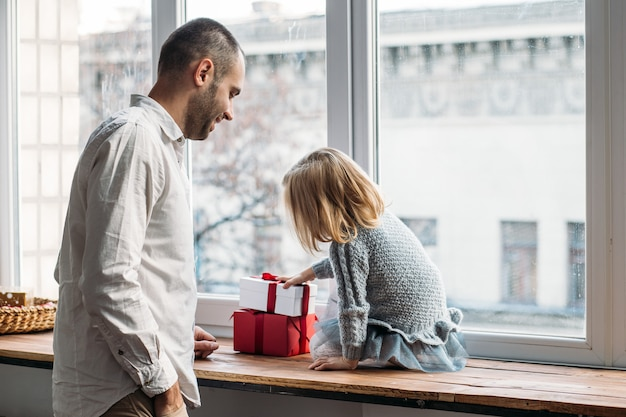 Hija y padre jugando con cajas de regalo junto a la ventana