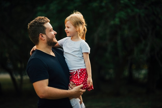 Hija y padre sonriendo el uno al otro