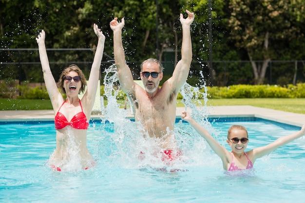 Hija y padres felices divirtiéndose en la piscina