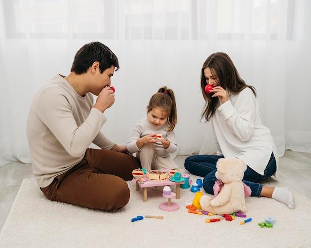 Hija y padres jugando juntos en casa