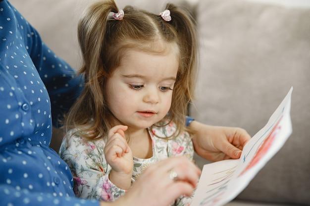 Hija pequeña con coletas. mamá embarazada con un vestido. hija con una foto.