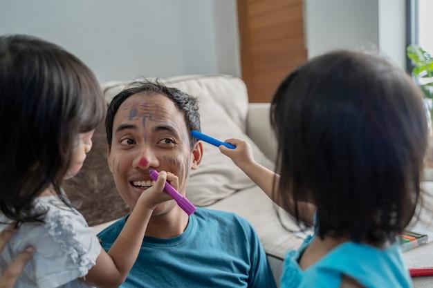 Hija pintando en la cara de su padre