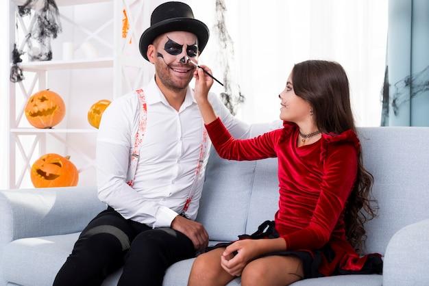 Hija pintando papás cara para halloween