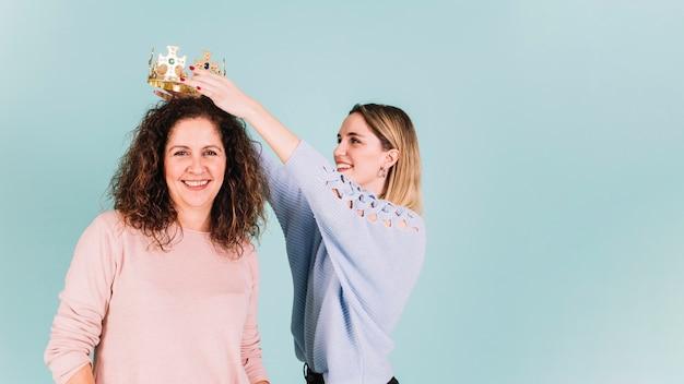 Hija poniendo corona en mamá