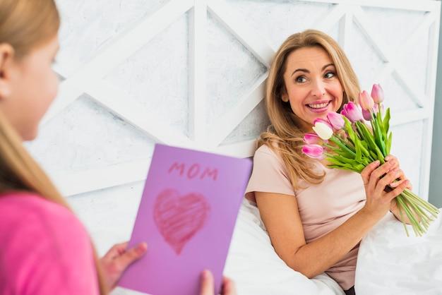 Hija que da la tarjeta de felicitación a la madre con los tulipanes