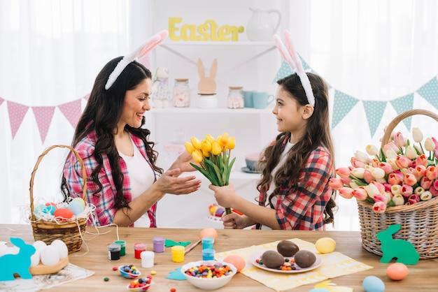 Hija que da tulipanes de flores amarillas a su madre con la preparación del día de pascua en casa
