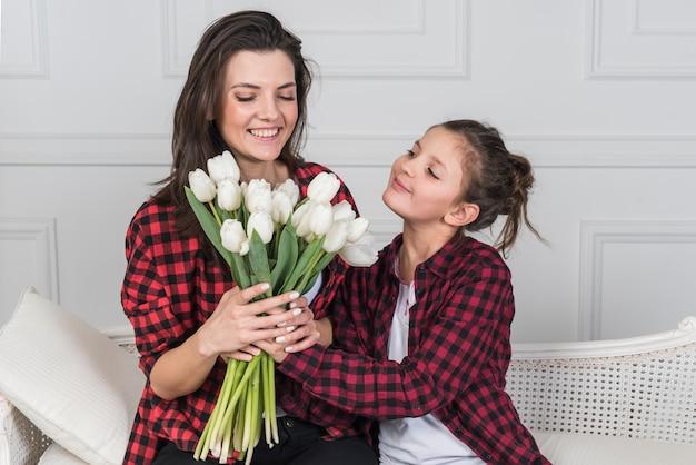 Hija que da tulipanes a la madre en el sofá
