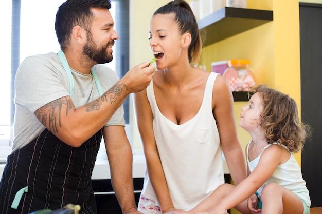 Hija que mira al padre que introduce el paprika a su madre