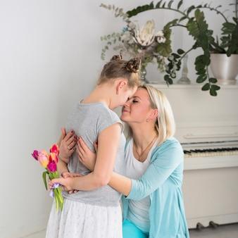 Hija que oculta tulipanes para la madre.