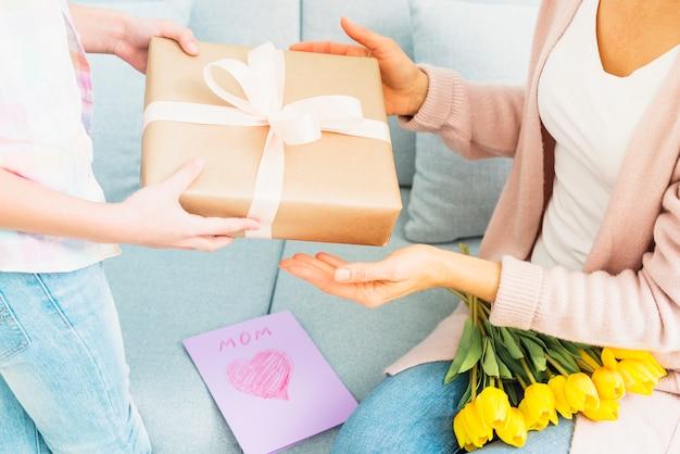 Hija que presenta una caja de regalo para mamá en la celebración del día de la madre
