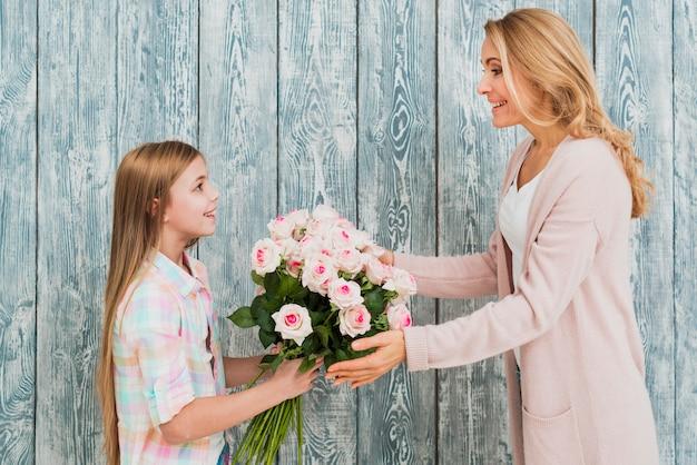 Hija que presenta a la madre ramo de rosas.