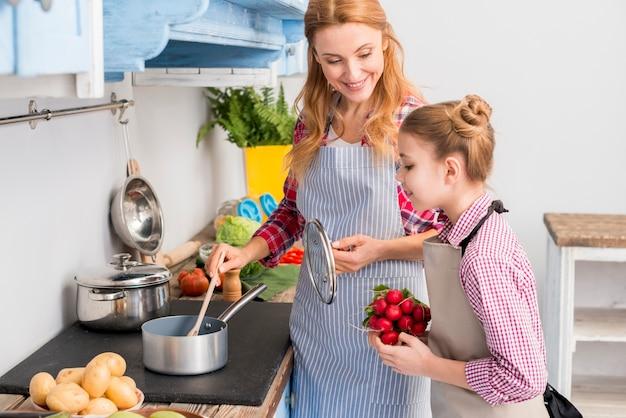 Hija que sostiene el nabo en la mano que mira a su madre que prepara la comida en la cocina