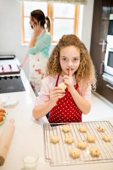 Hija que toma las galletas en secreto mientras que la madre habla en móvil