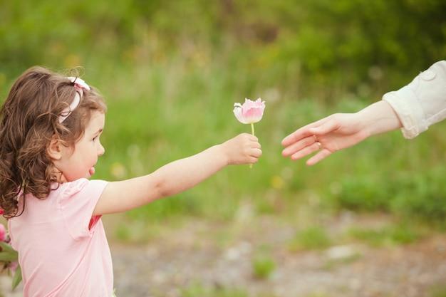 Hija regala una flor para mamá, día de la madre