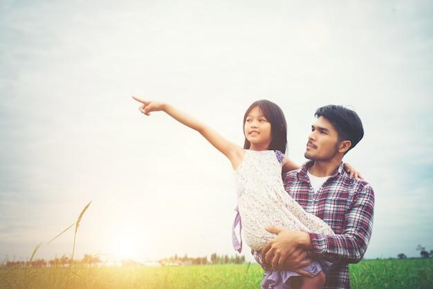 Hija señala lejos y que sonríe con su padre en los prados f