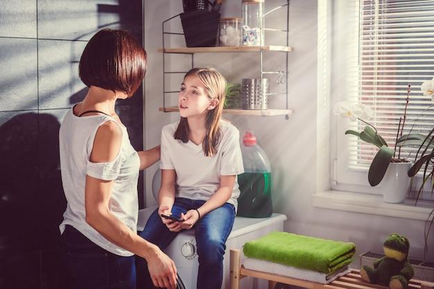 Hija sentada en la lavadora usando el teléfono y hablando con la madre
