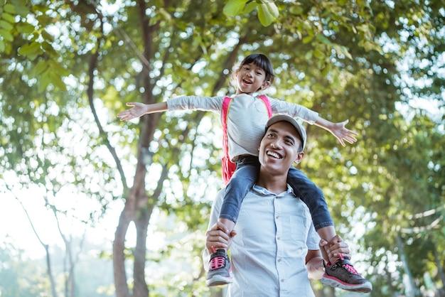 Hija sentada sobre el hombro del padre cuando va a la escuela