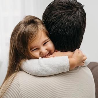 Hija sonriente abrazando a su papá en casa